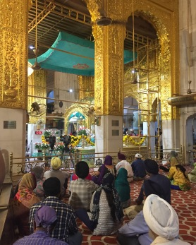 Seated around, praying or chanting along.